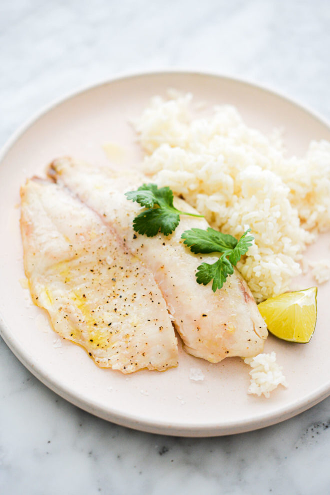 a pale pink plate with a cooked tilapia filet, white rice, a lime wedge, and cilantro sprigs sitting on it, on a marble surface