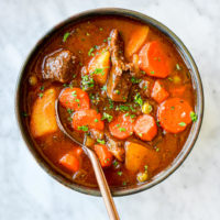 a bowl of slow cooker beef stew with a spoon sticking out of it sitting on a marble surface