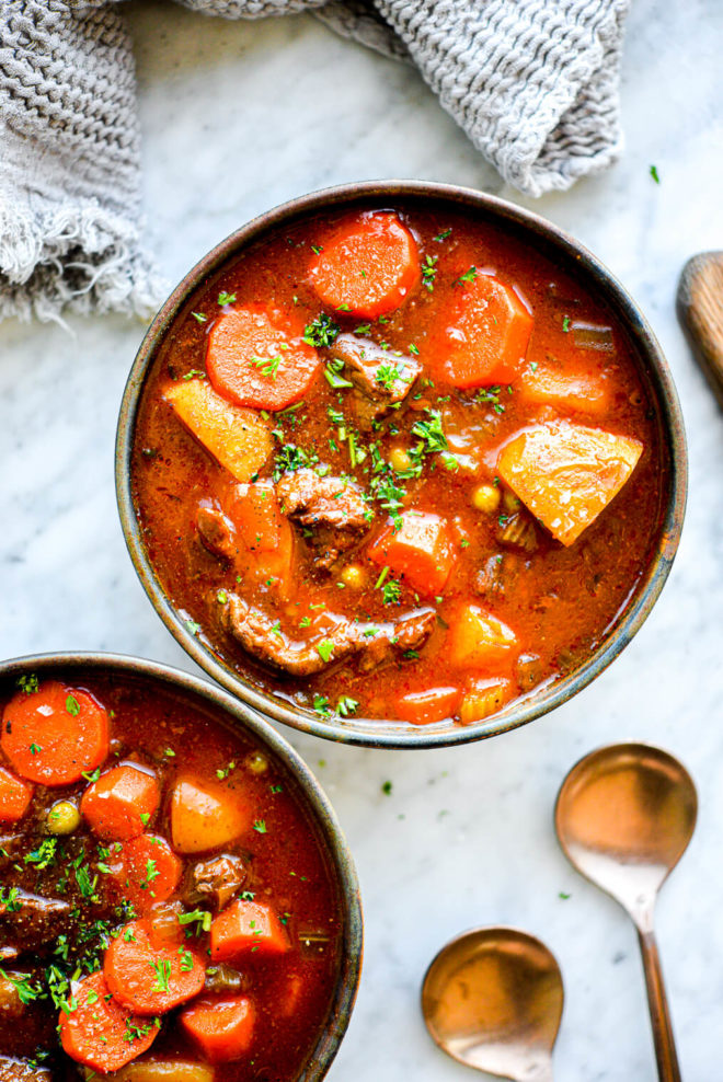 two bowls of beef stew sitting next to spoons on a marble surface