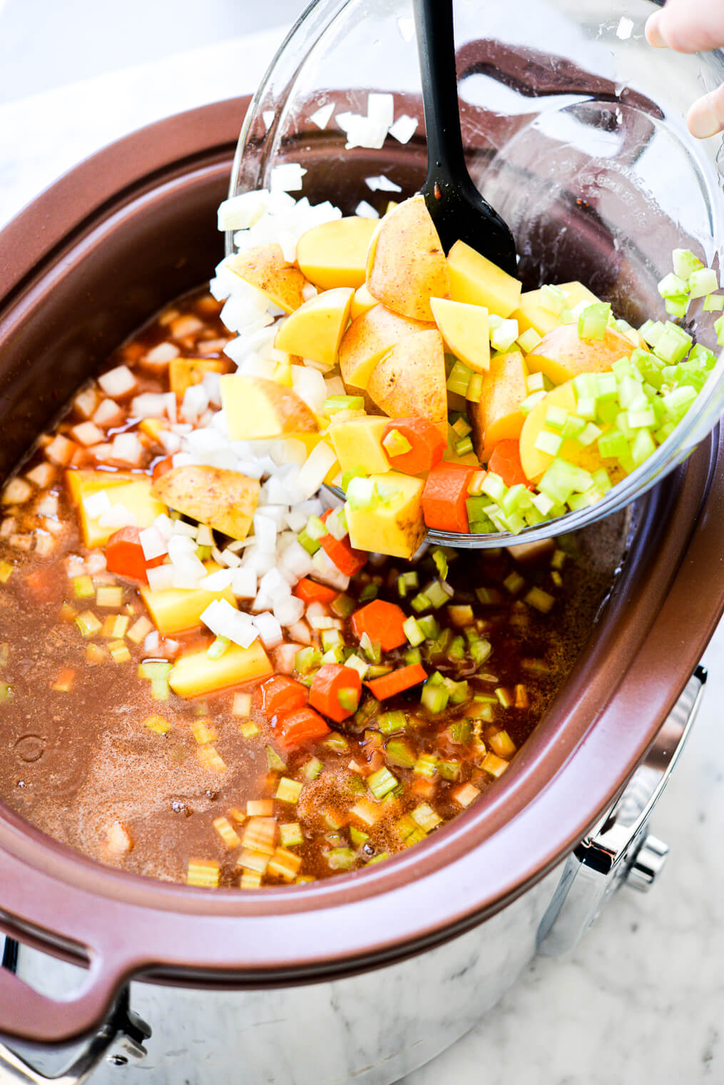 a large slow cooker of beef stew with someone pouring chopped stew veggies into the slow cooker