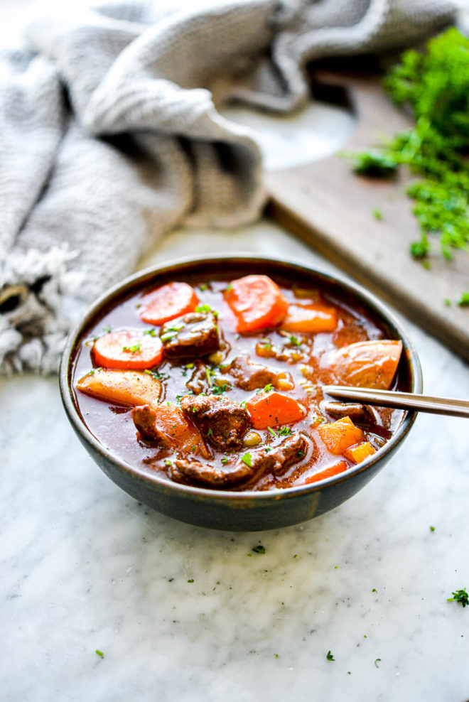 a bowl of slow cooker beef stew with a spoon sticking out of it sitting in front of parsley on a marble surface