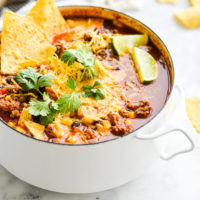 a small white pot of taco soup garnished with lime wedges, shredded cheese, cilantro, and tortilla chips