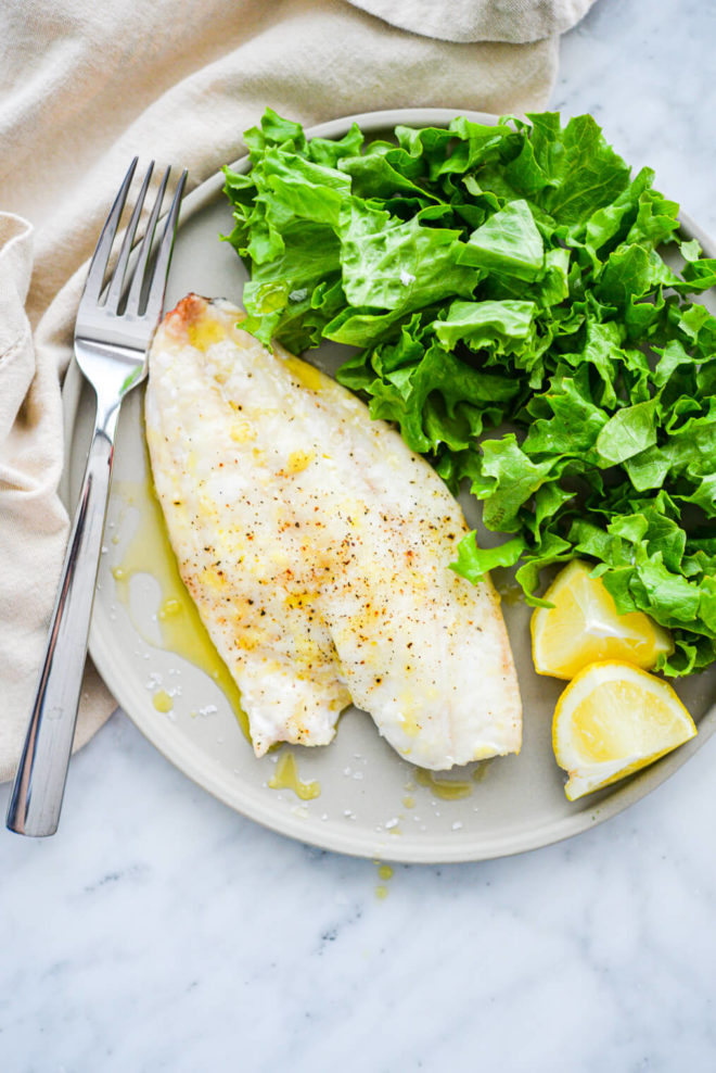 a light gray plate with a filet of red snapper next to a bed of lettuce and lemon wedges