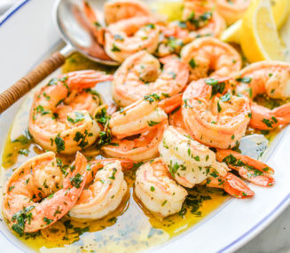a oblong white dish filled with shrimp scampi sitting on a marble surface