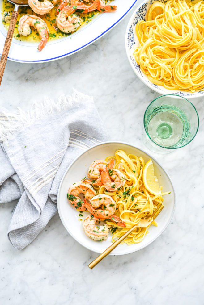 a shallow white bowl filled with gluten free noodles and shrimp scampi