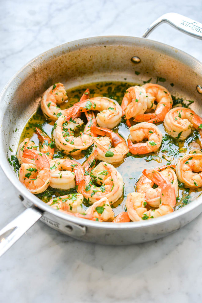 a non stick high walled pan of shrimp scampi sitting on a marble surface