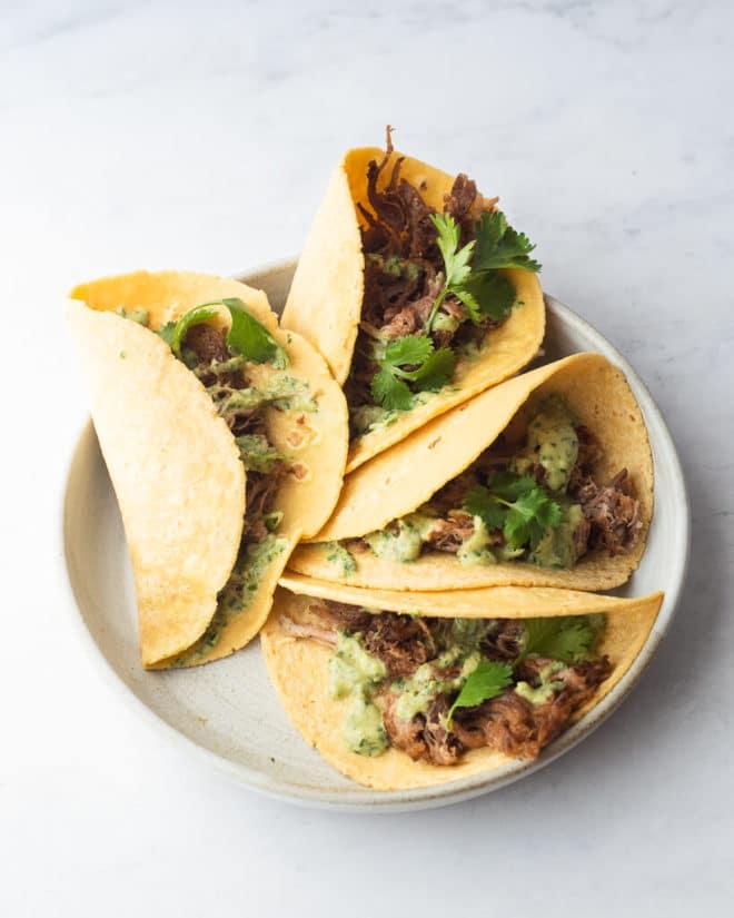 a plate of 4 carnitas tacos topped with creamy avocado verde sauce and cilantro