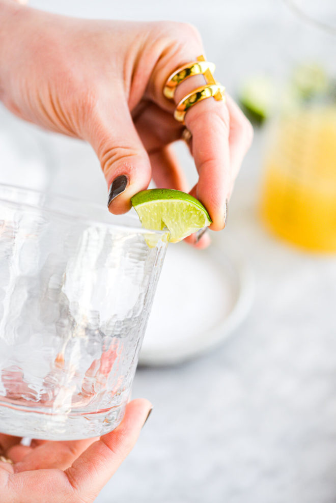 a woman squeezing lime juice around the rim of a margarita glass before salting it