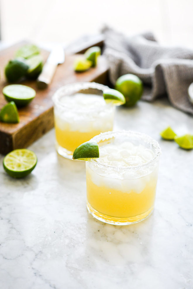 two salt rimmed glasses filled with margarita in front of sliced limes