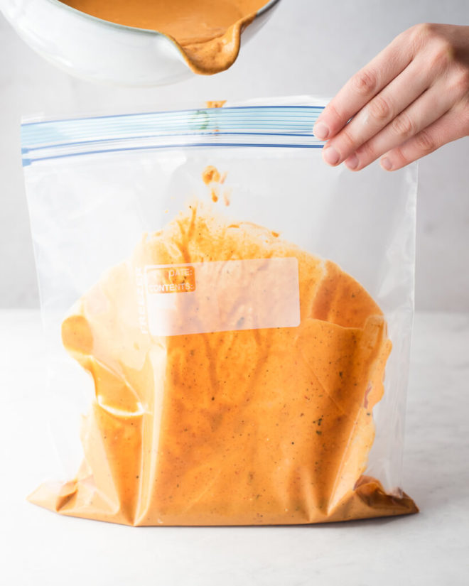 a person holding a large gallon size ziplock bag with one hand and pouring chicken tikka masala sauce into the bag with the other hand
