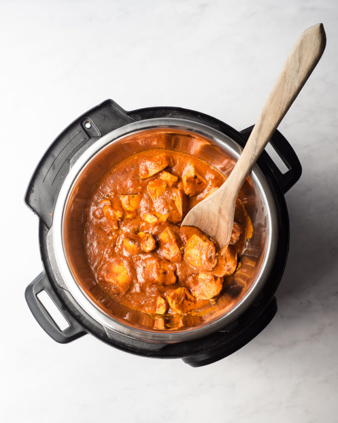 instant pot chicken tikka masala cooked in the instant pot with a wooden spoon resting in the instant pot too