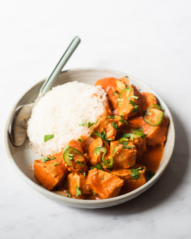 a plate of tikka masala and a bed of rice with a spoon resting on the plate