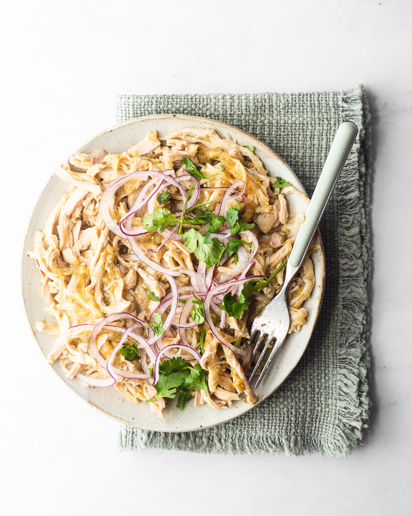 a plate of shredded salsa chicken garnished with cilantro and purple onion sitting on a green kitchen towel