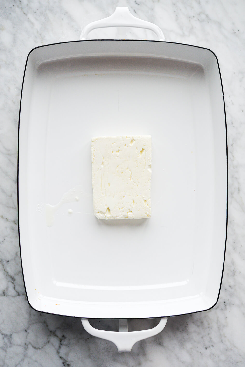 a block of feta cheese sitting in a white baking dish on a marble surface