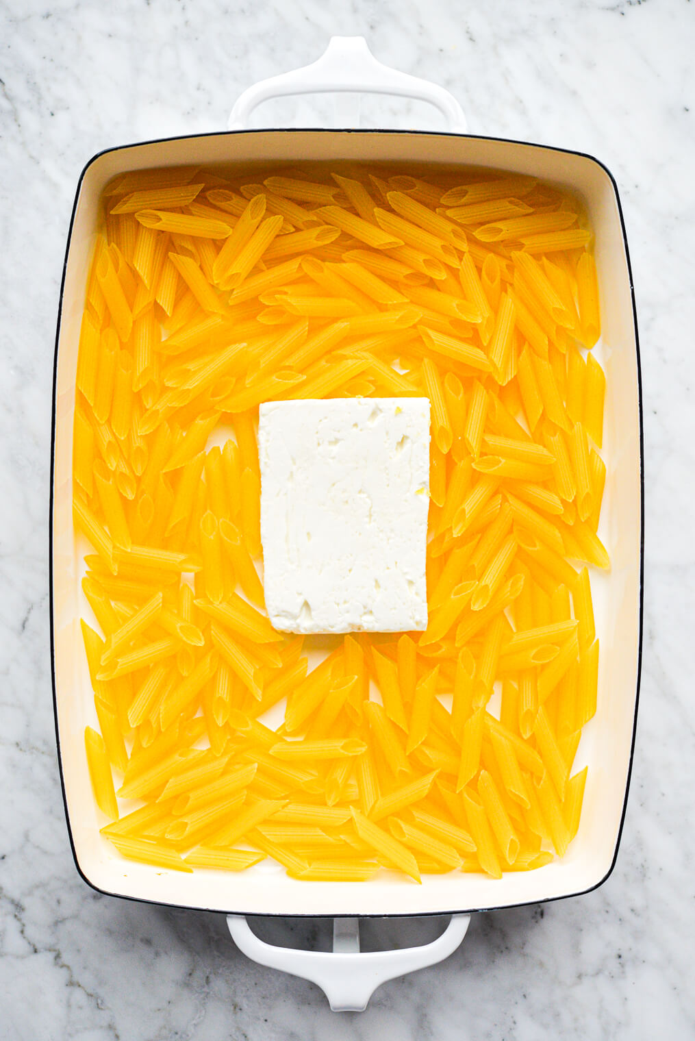 a white baking dish with uncooked penne pasta and a block of feta cheese in it