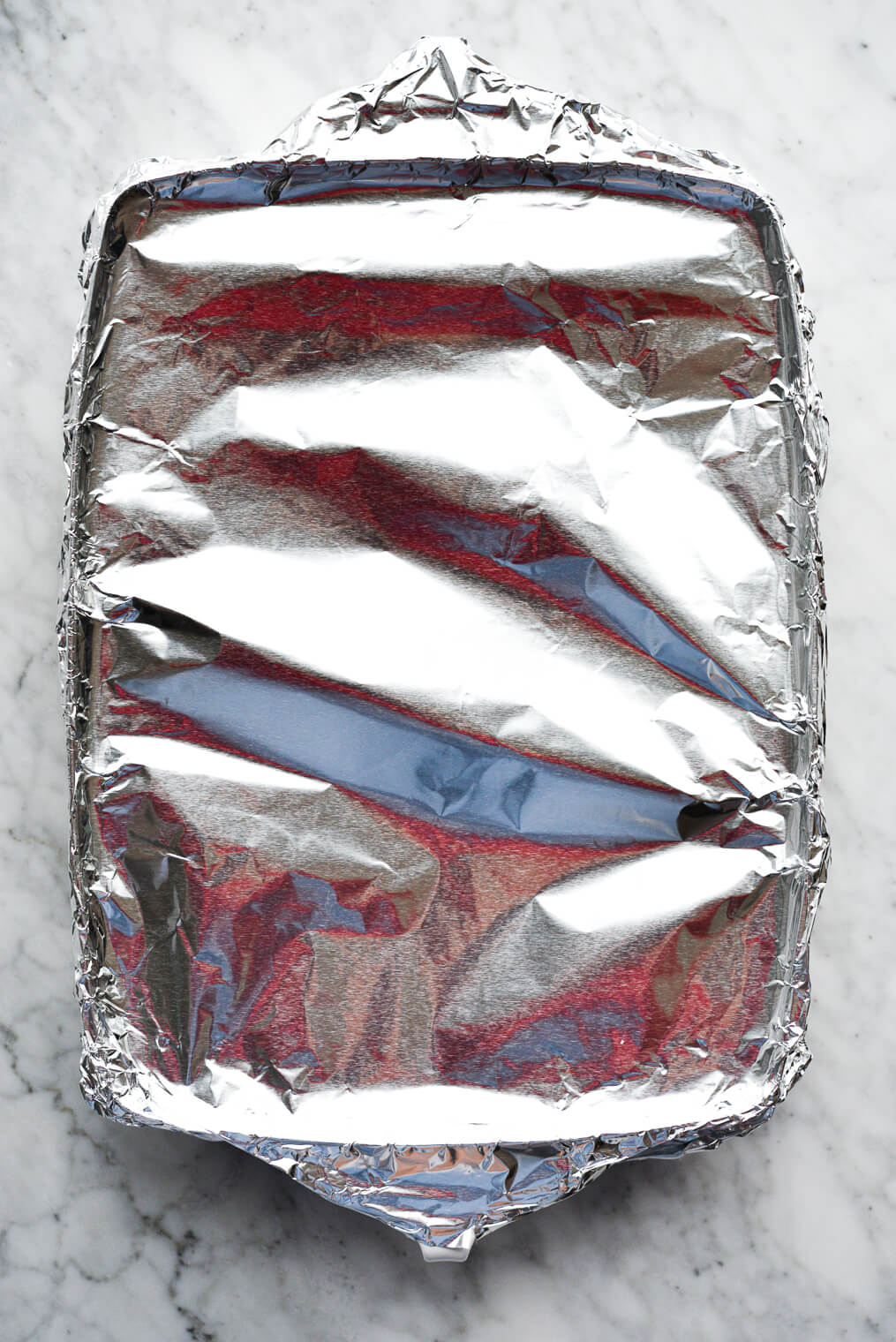 a baking dish covered tightly with foil sitting on a marble surface