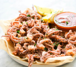 a parchment paper lined plate with calamari and a red sauce sitting on it