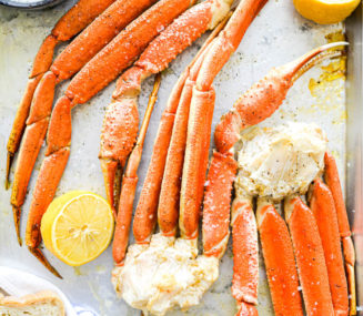 a crab bake sheet pan with halved lemons, crab legs, and butter on it