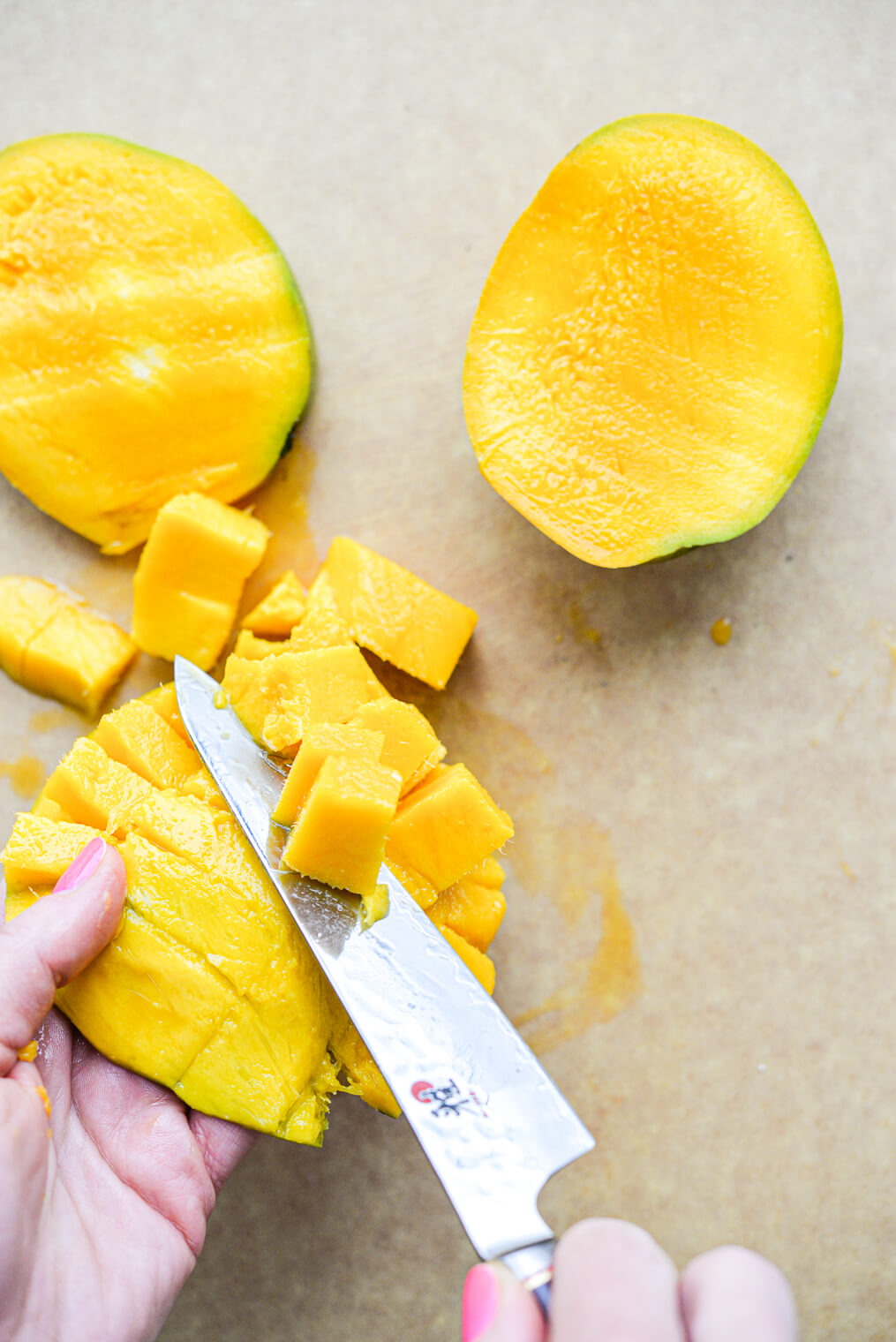 a woman holding the flesh of a mango as she slices the cubes of mango off of it