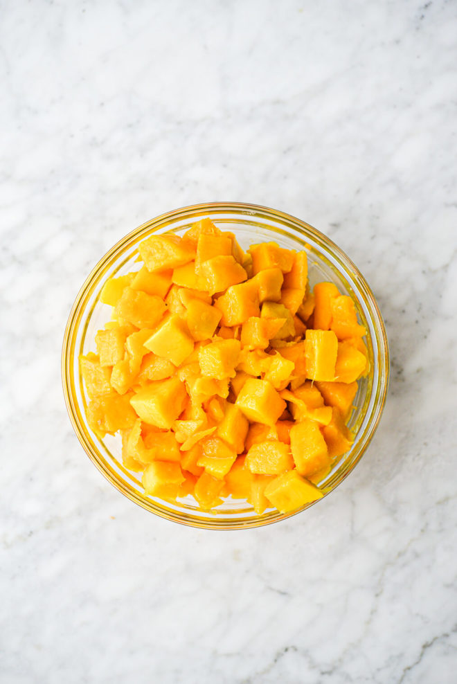 a clear glass bowl of cubed mango sitting on a marble surface