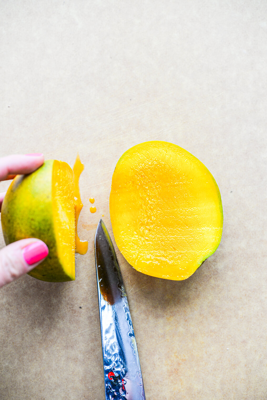 a woman holding half of a mango upright with a knife in the other hand