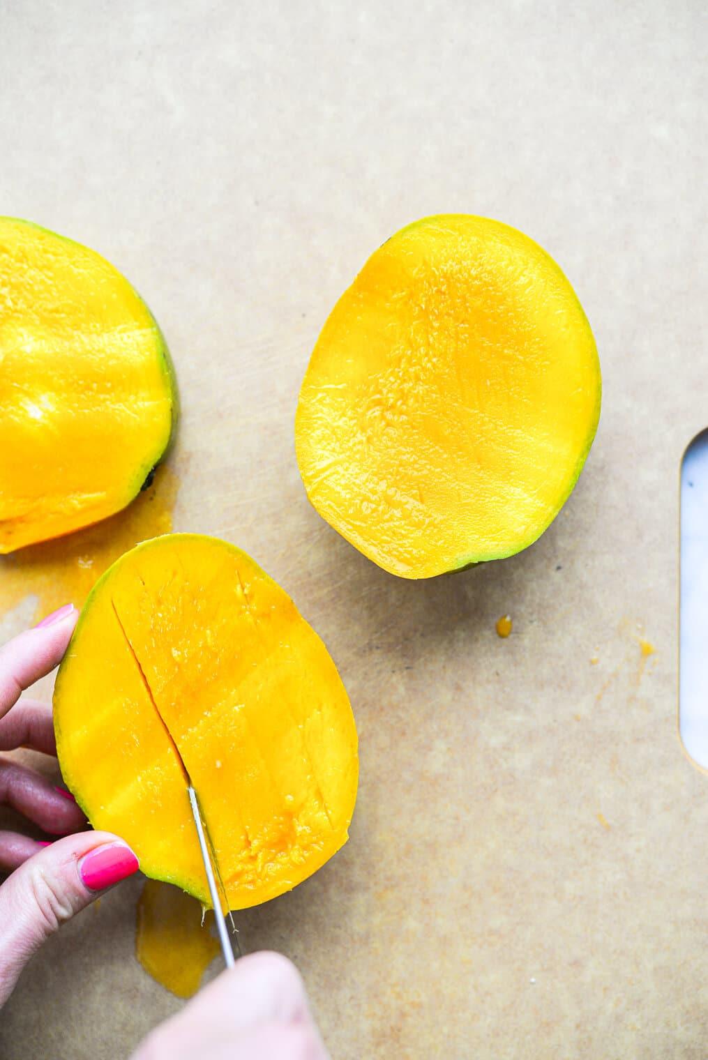 a woman cutting a halved mango on a cutting board