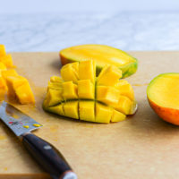 a halved mango with the flesh cut into cubes and the flesh of the mango turned inside out