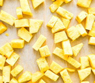 a parchment paper lined sheet pan with cubed pineapple laying on it