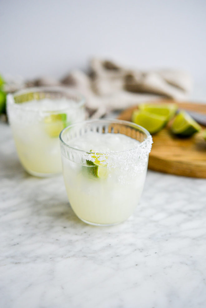 two salt rimmed glasses of keto margarita sitting in front of a cutting board with lime juice wedges sitting on it