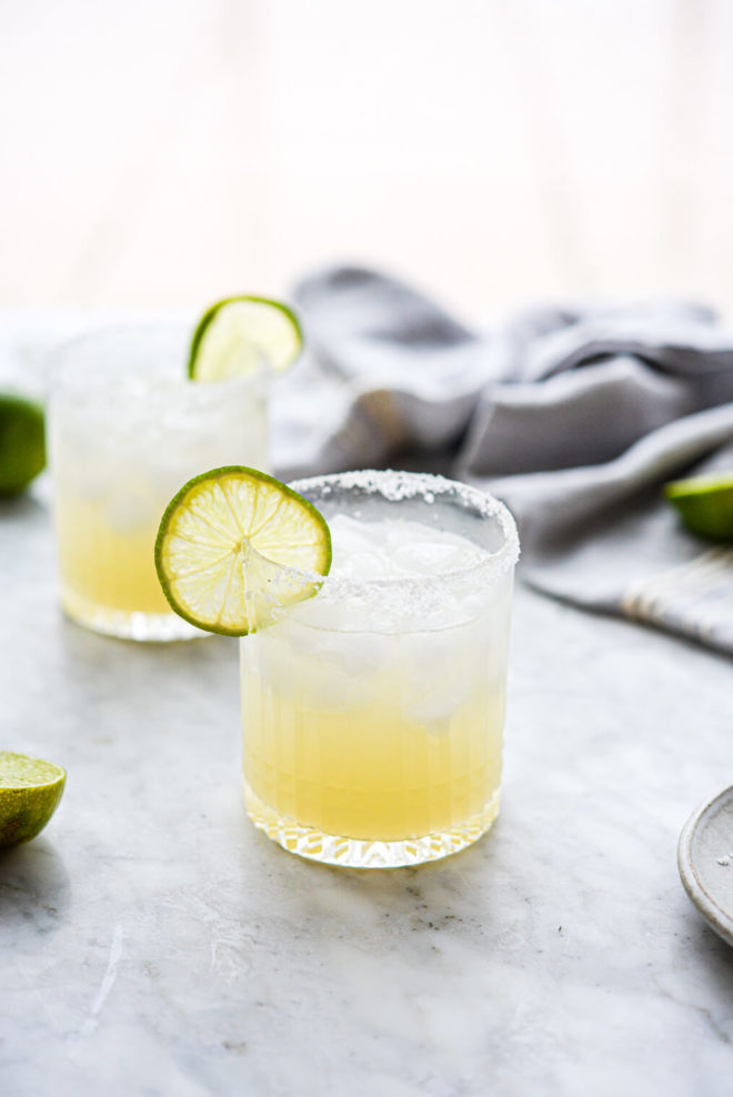 two salt rimmed glasses of skinny margarita sitting on a marble surface