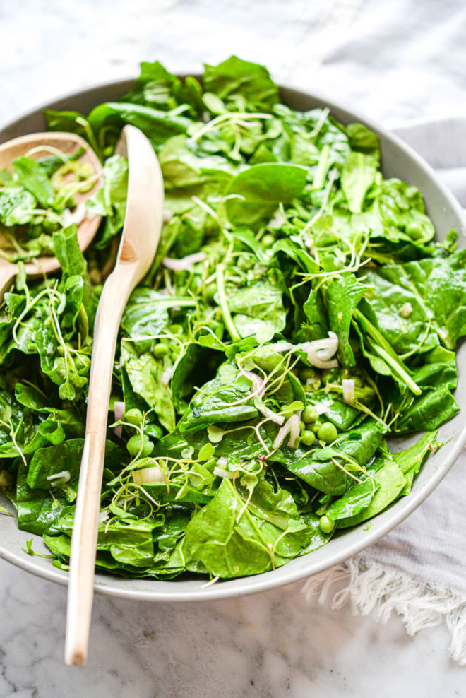 a large gray bowl filled with a bright green spinach salad with two salad spoons sticking out of the bowl