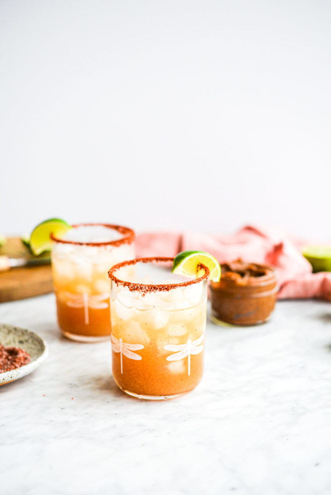a tamarind margarita in a glass with dragonflies on it and rimmed with chili salt