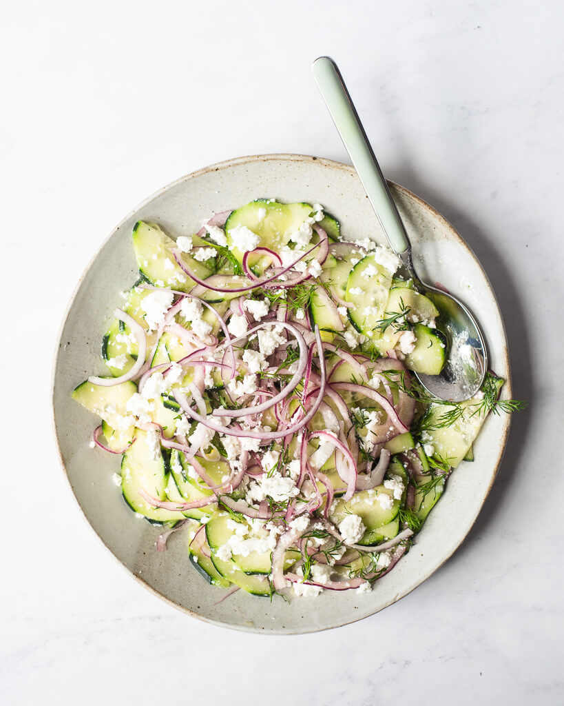 a greek cucumber salad made of thinly sliced cucumber, red onion, feta cheese, and dill sitting on a light gray plate