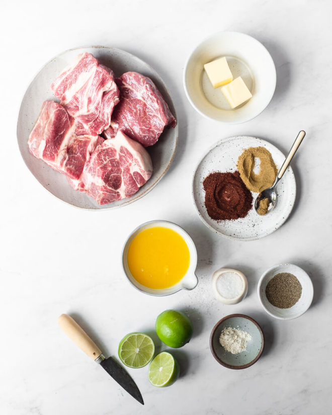 all of the ingredients for slow cooker carnitas sitting on a marble surface