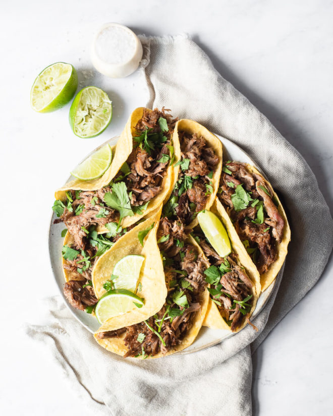 a plate of pork carnitas tacos garnished with lime wedges and cilantro