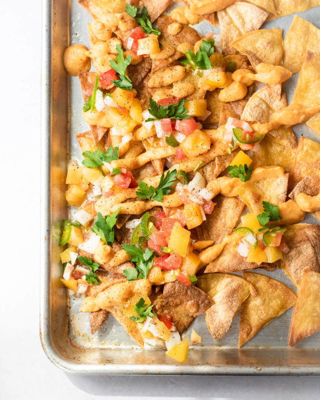 a sheet pan of hand fried corn tortilla chips topped with vegan nacho cheese, pico de gallo, and cilantro
