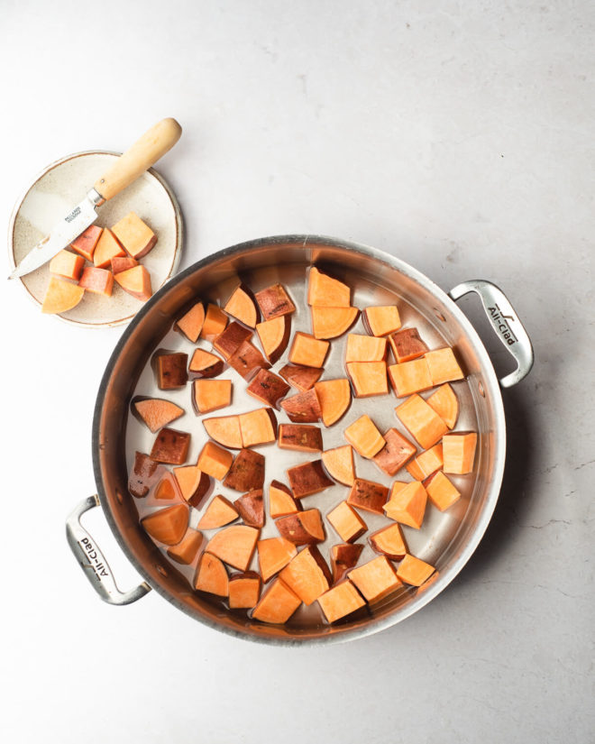 a large pot of chopped sweet potatoes in water with a small plate of chopped sweet potatoes and a knife next to it