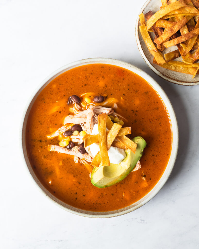 a bowl of creamy chicken tortilla soup garnished with avocado, sour cream, and fried tortilla strips