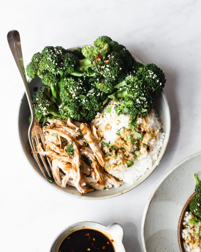 teriyaki chicken bowl with white rice and broccoli garnished with sesame seeds and red pepper flakes on a marble surface
