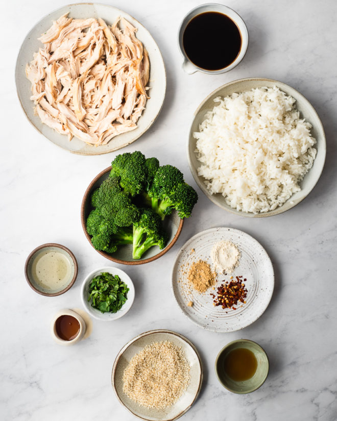 bowls of shredded chicken, teriyaki sauce, white rice, broccoli, and spices on a marble surface