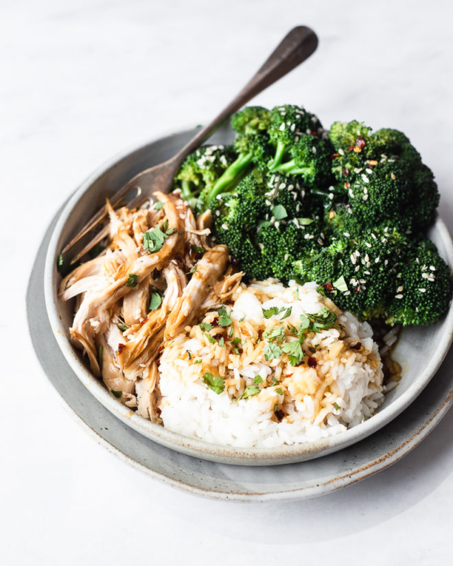 side view of a teriyaki chicken bowl filled with shredded chicken, broccoli florets, and white rice drizzled with teriyaki sauce, sesame seeds, and red pepper flakes