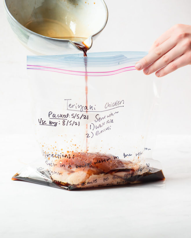 freezer meal teriyaki chicken in a labeled ziplock bag on a marble surface