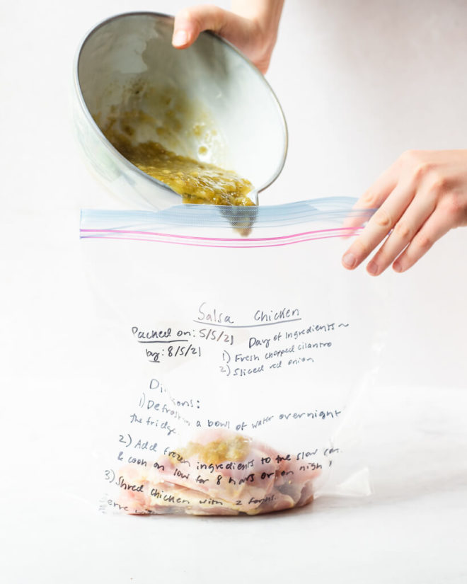 freezer meal salsa chicken in a labeled ziplock bag on a marble surface