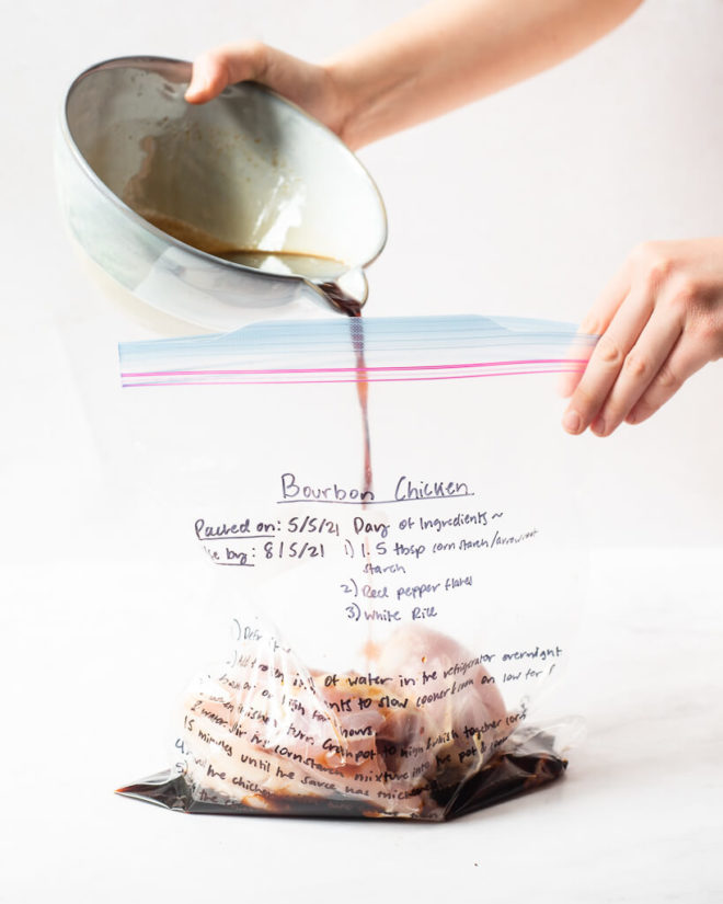 the ingredients for bourbon chicken being poured into a labeled freezer bag