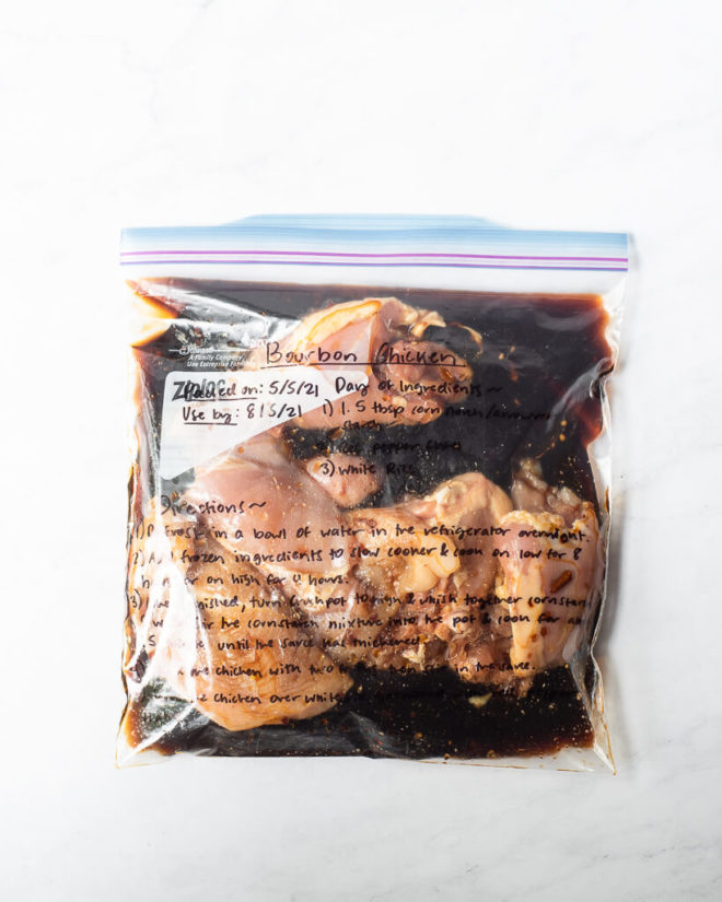freezer meal bourbon chicken in a labeled ziplock bag on a marble surface