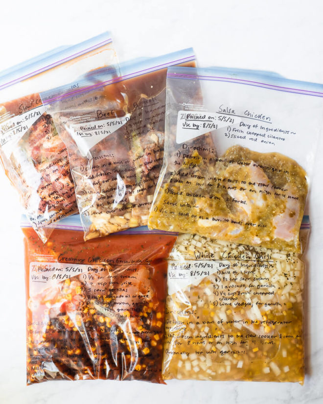 5 freezer meals in gallon size labeled ziplock bags laying on a white surface