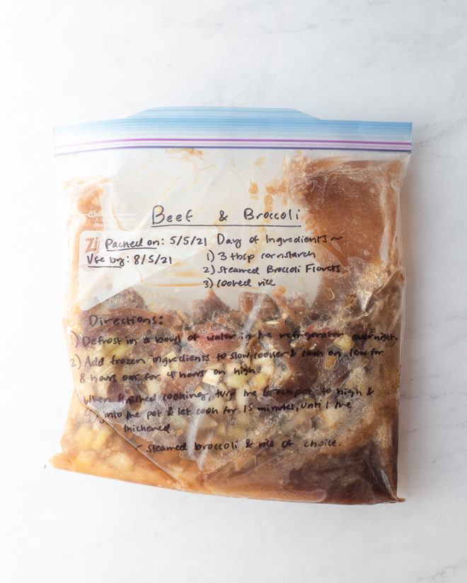 freezer meal beef and broccoli in a labeled ziplock bag on a marble surface