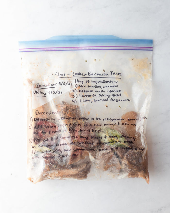 freezer meal slow cooker barbacoa tacos in a labeled ziplock bag on a marble surface