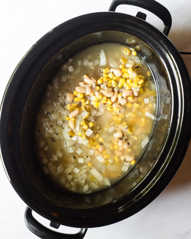 a raw, thawed freezer meal in a slow cooker sitting on a marble surface
