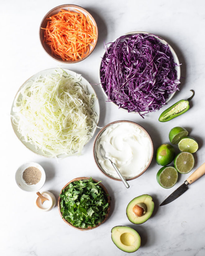 the ingredients for creamy Mexican coleslaw sitting on a marble surface